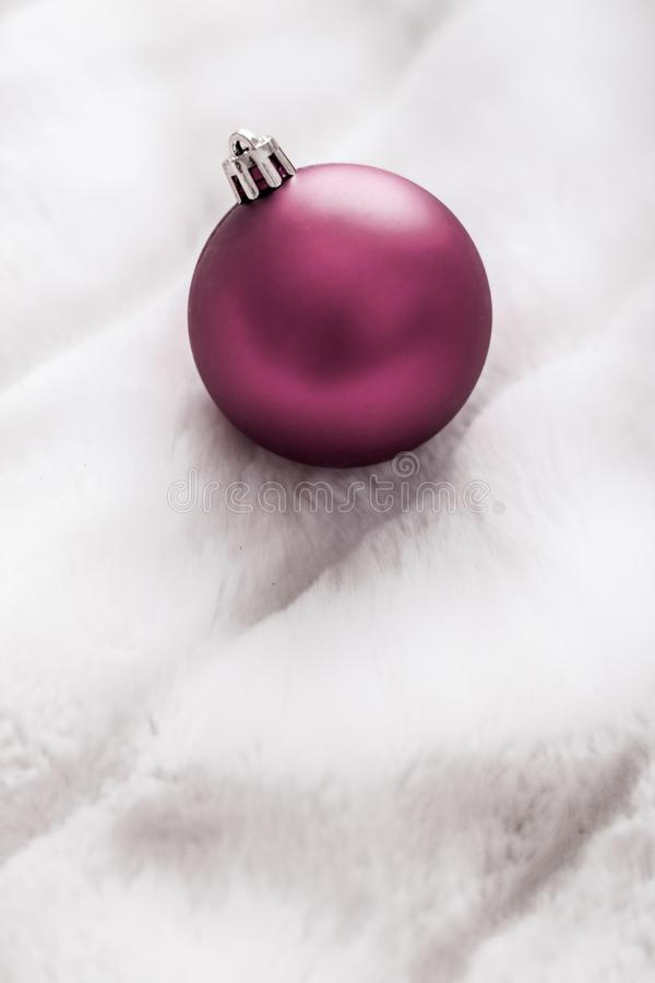 Purple Christmas baubles on white fluffy fur backdrop, luxury winter holiday design background royalty free stock photography