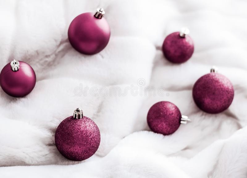 Purple Christmas baubles on white fluffy fur backdrop, luxury winter holiday design background. Gift decor, New Years Eve and happy celebration concept - Purple stock photography