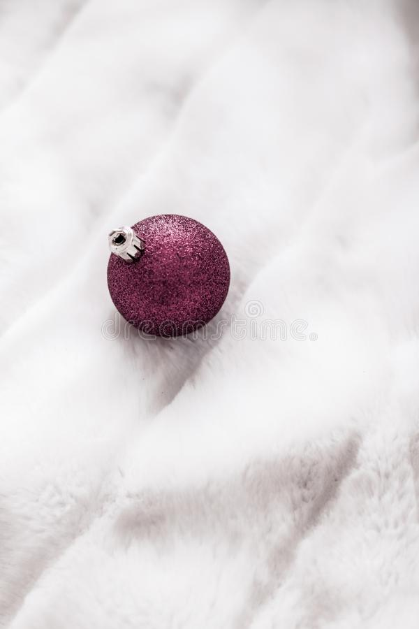 Purple Christmas baubles on white fluffy fur backdrop, luxury winter holiday design background. Gift decor, New Years Eve and happy celebration concept - Purple royalty free stock images