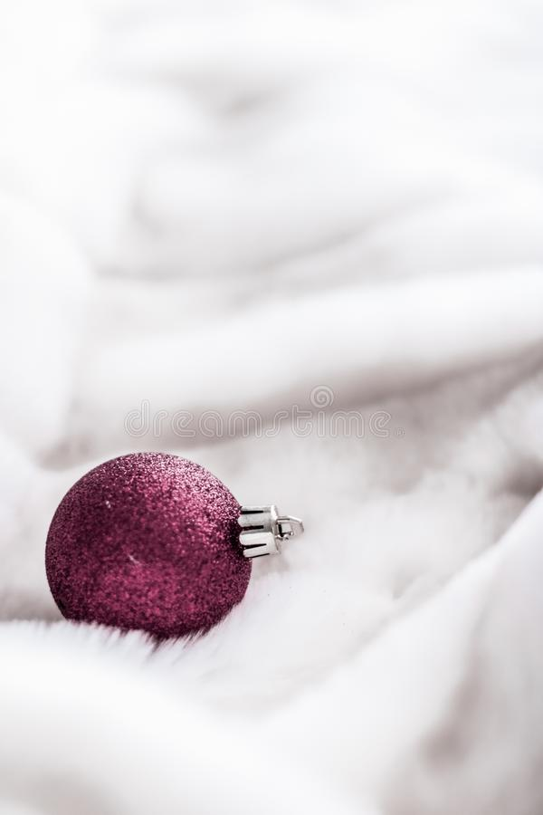 Purple Christmas baubles on white fluffy fur backdrop, luxury winter holiday design background stock photo