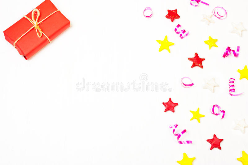 Gift with decor from stars, confetti. The composition of the present in red wrapping paper and stars, Christmas decorations. Christmas, New Year`s background stock images