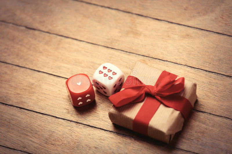Gift and dice. Beautiful gift and small dice on the wonderful brown wooden background stock image