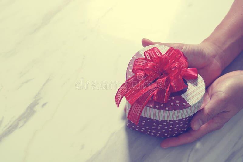 gift die, mensenhand die een de giftdoos van de hartvorm in een gebaar houden geven stock fotografie