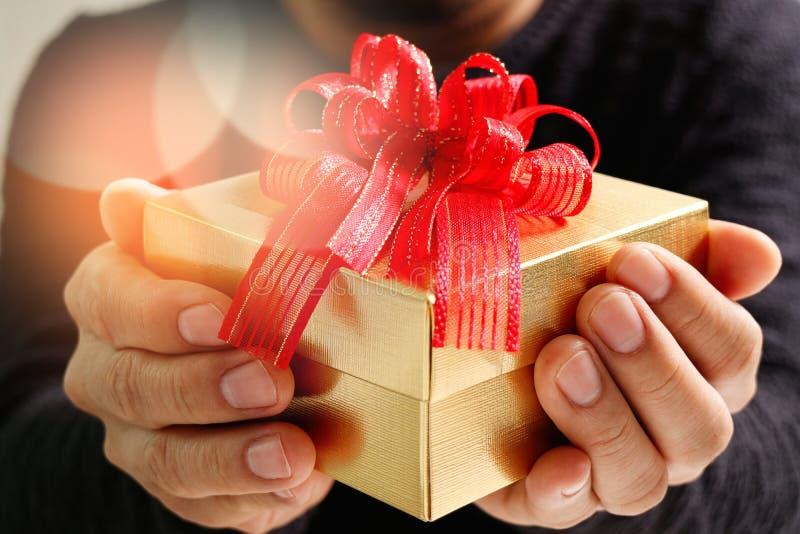 gift die, mensenhand die een giftdoos in een gebaar van het geven houden geven B royalty-vrije stock foto's