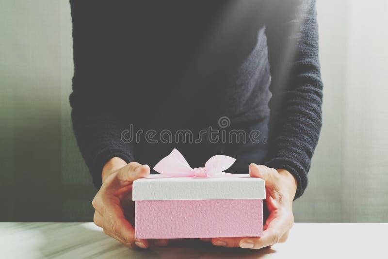 gift die, mensenhand die een giftdoos in een gebaar van het geven houden geven B stock afbeeldingen