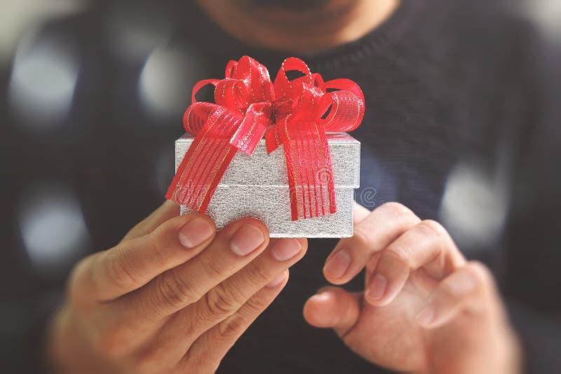 gift die, mensenhand die een giftdoos in een gebaar van het geven houden geven B royalty-vrije stock foto