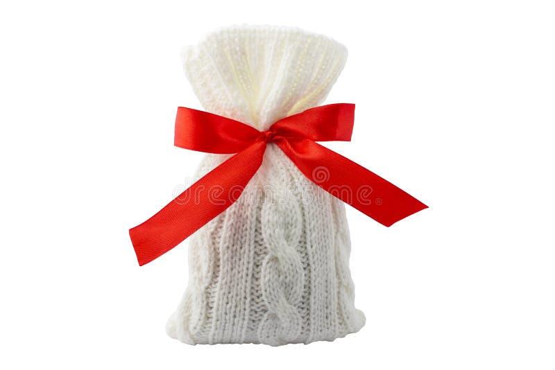 Gift in een breiende zak met een rood lint Op een witte achtergrond stock fotografie