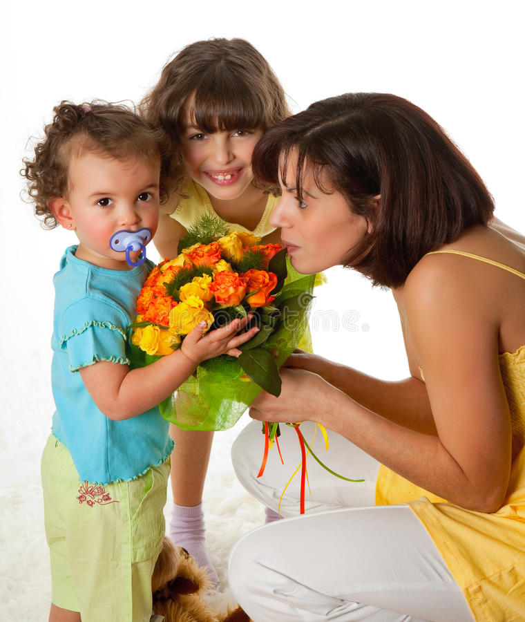 Gift from the girls. Two little girls giving flowers to mom on mother's day stock photo