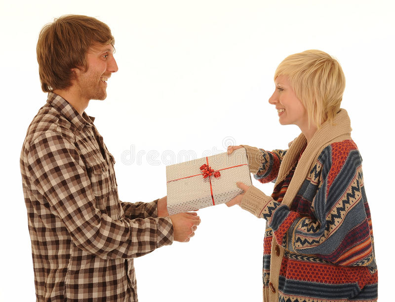 Gift giving. A smiling young woman faces her male friend as she gives him a gift royalty free stock photography