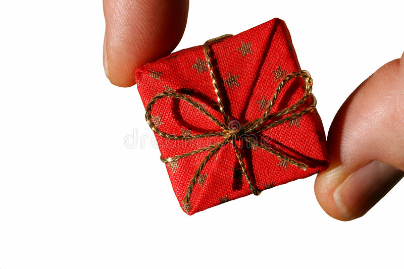 Gift Giving Isolated. A thumb and index finger hold a small red gift box with gold ribbon. Isolated on a white background. Great for gift giving, holidays royalty free stock photos