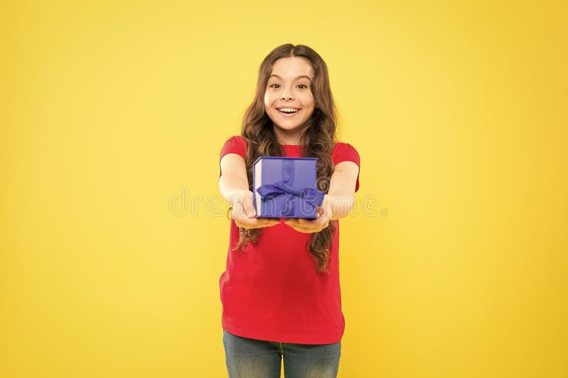 Gift giving makes her happy. Adorable little girl giving blue present box on yellow background. Cute small child enjoy stock photos