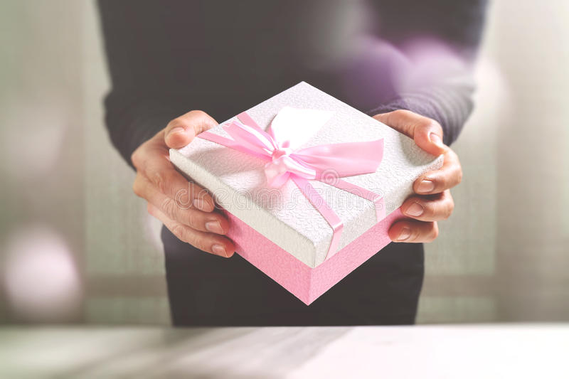 Gift giving,man hand holding a gift box in a gesture of giving.blurred background,vintage effect stock photos