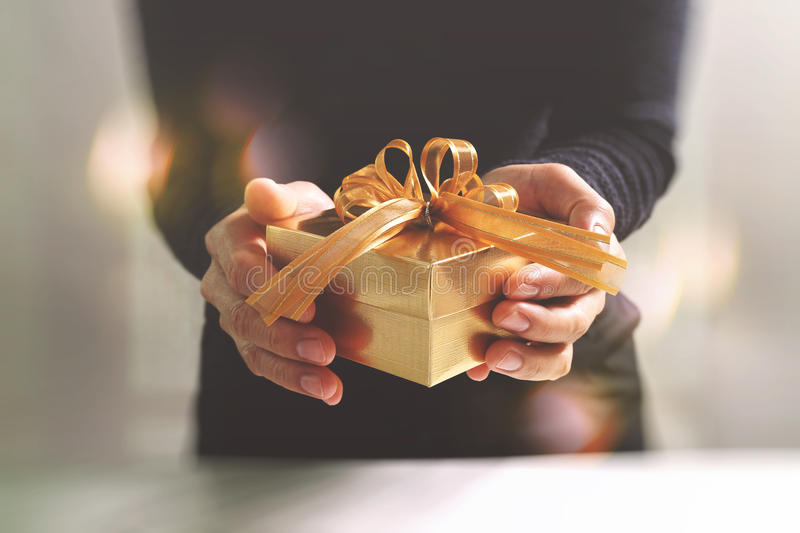 gift giving,man hand holding a gift box in a gesture of giving.blurred background,bokeh effect stock photos