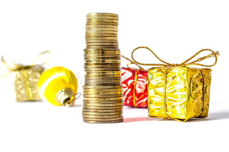 Gift in a gold box with a bow on a pile of gold coins on a background of other gifts isolated on a white royalty free stock photos