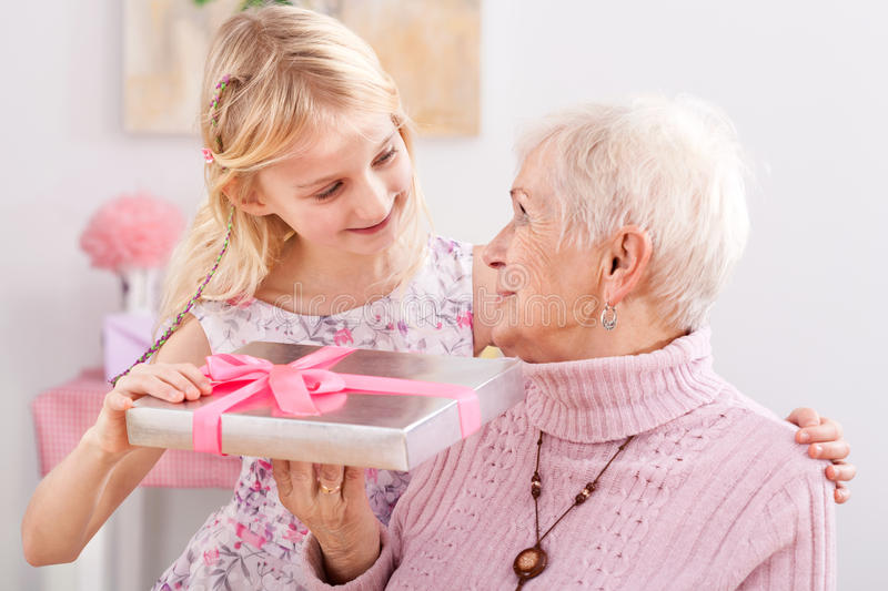 Gift for grandma. A granddaughter giving her grandma an elegantly packed gift royalty free stock photos