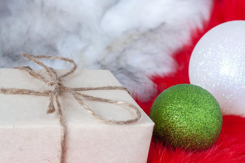 Gift in gray paper and a green and white Christmas ball on fluffy white and red fur. On the present is a hemp rope bow. Selective focus on the bow and green stock photo