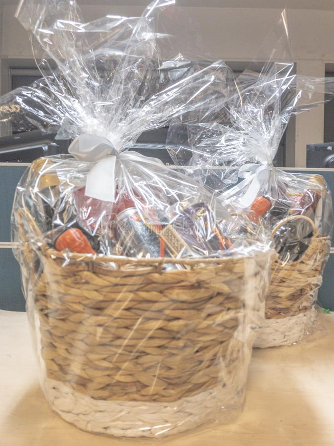 Gift hamper basket. Wrapped in plastic sheet sitting on a table ready for presentation royalty free stock images