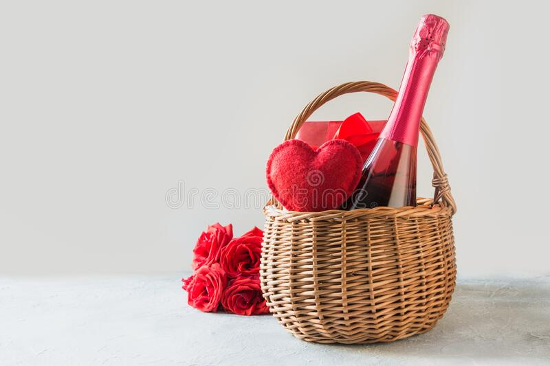 Gift hamper, bouquet of red roses,heart, bottle of champagne on white. Valentines day card. Romantic gift. Valentines day gift hamper, heart, bouquet of red royalty free stock images