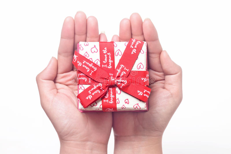 Gift on the hand. On hand gift, it tied with red ribbon stock photo