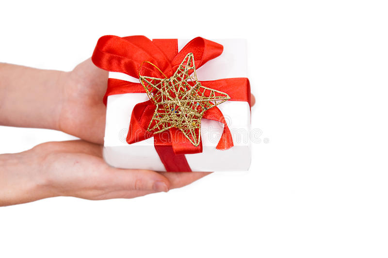 Gift in hands. Hands holding Christmas gift over white royalty free stock photo