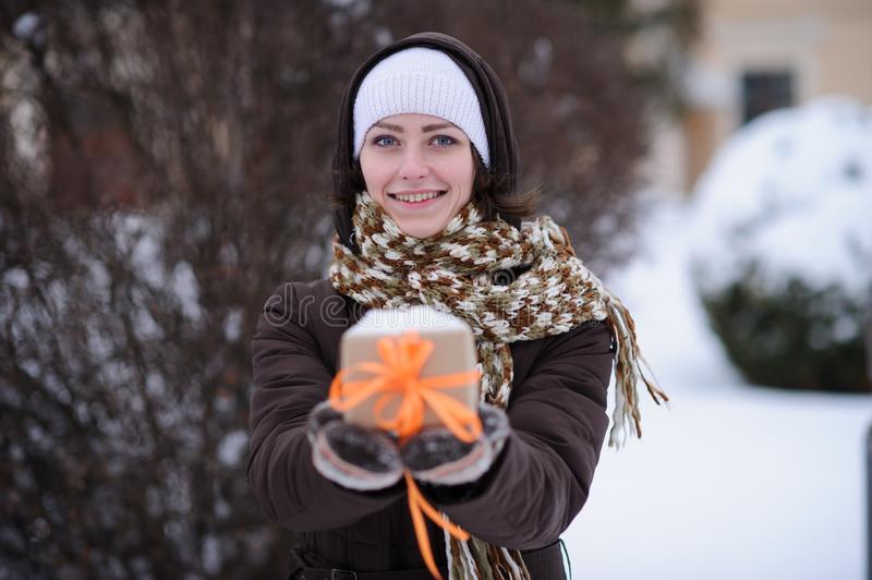 Gift in hands. winter season. Gift with orange stripes in hands in winter royalty free stock photos