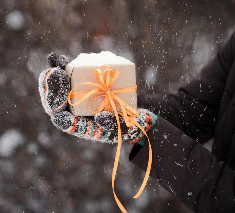Gift in hands in winter season. Gift with orange stripes in hands in winter stock photos