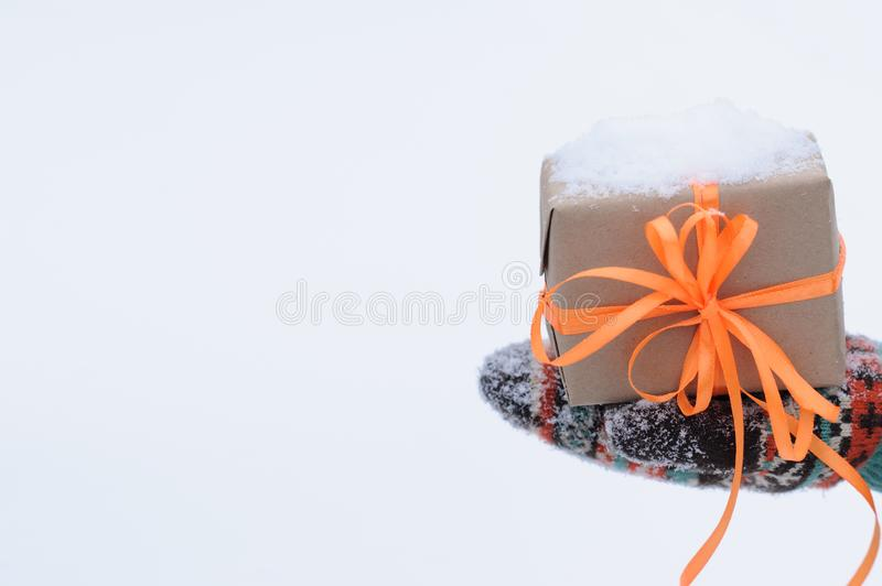 Gift in hands in winter season. Gift with orange stripes in hands in winter royalty free stock photo