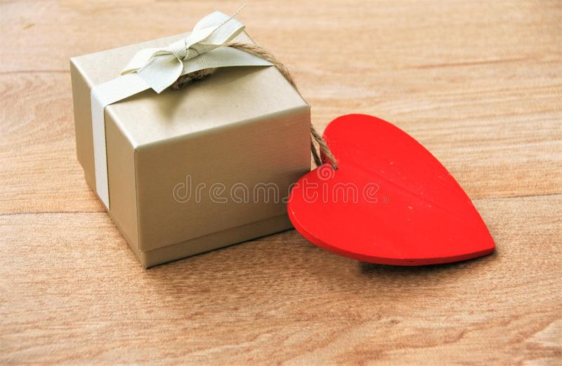 Gift with heart. Gift box with bow and a red heart hanging on a wooden table with copy - space stock photos
