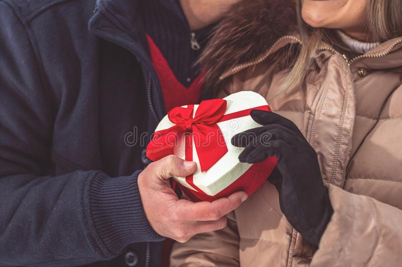 Gift hearts - hand of guy giving his girlfriend Christmas presen royalty free stock images