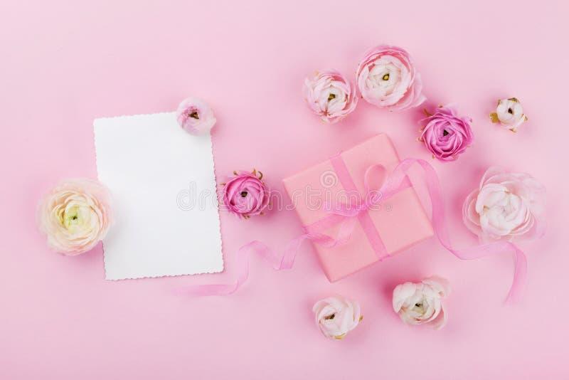Gift of heden, document lege en mooie bloem op roze bureau van hierboven voor huwelijksmodel of groetkaart op de dag van de vrouw royalty-vrije stock afbeelding