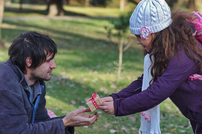 Gift for homeless. A little girl donate a gift for a homeless men in a park. This is really kindness stock photo