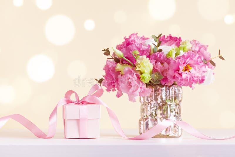 Gift of huidige doos en mooi bloemenboeket in vaas op pastelkleur bokeh achtergrond Groetkaart voor moederdag stock foto's