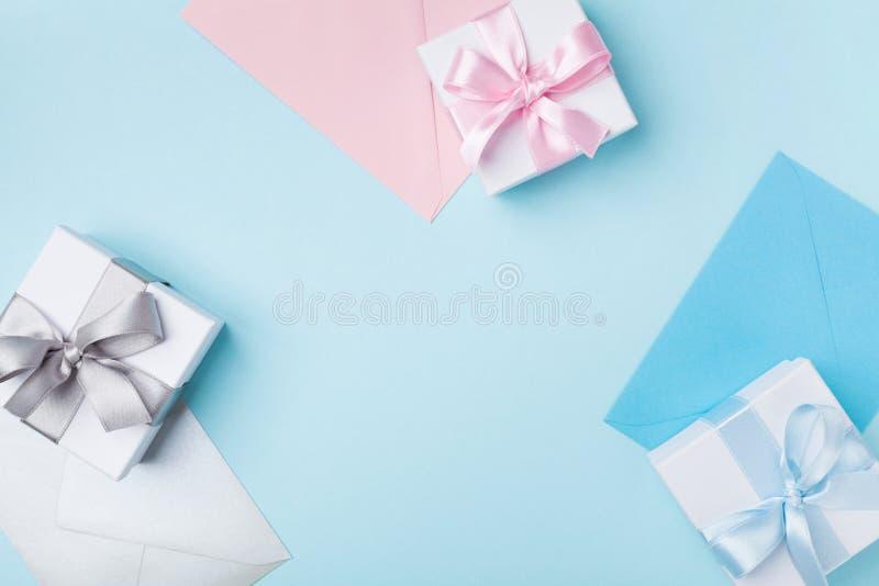 Gift of huidige vakje en kleurrijke enveloppen op de blauwe mening van de lijstbovenkant Groet voor vakantie Vlak leg stock afbeeldingen