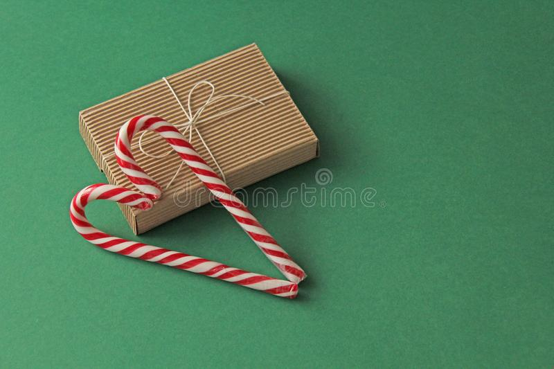 Gift Kraft Brown Color Box and Candy Canes Red and White in Heart Shape Lies on the Green Background, View From the Top. For your. Decoration of Postcards, New stock image