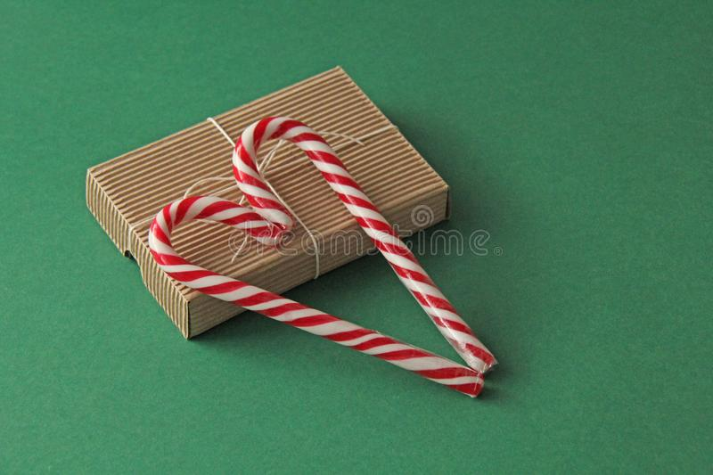 Gift Kraft Brown Color Box and Candy Canes Red and White in Heart Shape Lies on the Green Background, View From the Top. For your. Decoration of Postcards, New royalty free stock images