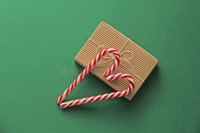 Gift Kraft Brown Color Box and Candy Canes Red and White in Heart Shape Lies on the Green Background, View From the Top. For your. Decoration of Postcards, New stock photography