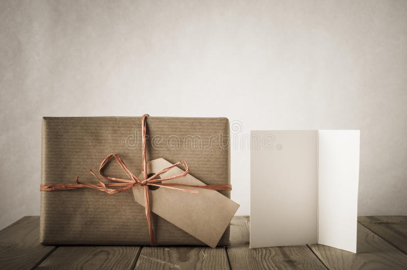 Gift with Label and Card. A gift box wrapped in brown paper and tied with raffia with blank label facing front. Next to a blank open card on an old, weathered stock photo