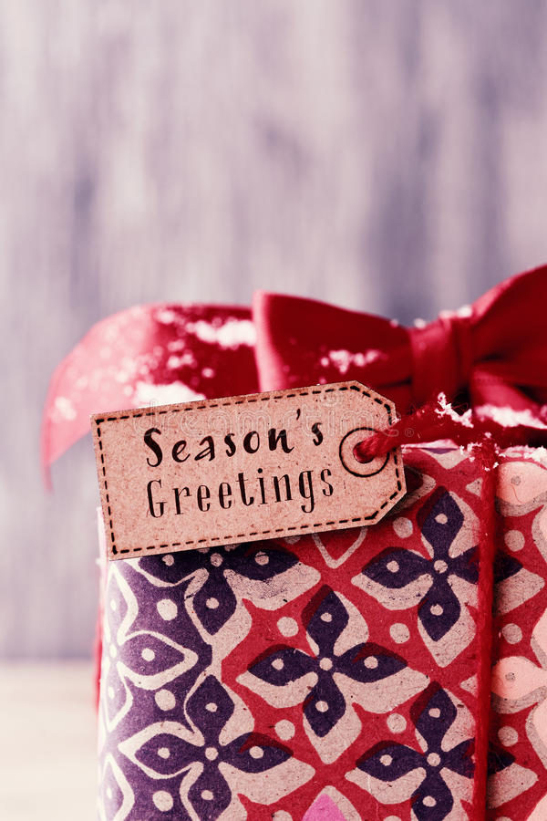 Gift with a label with the text seasons greetings stock image
