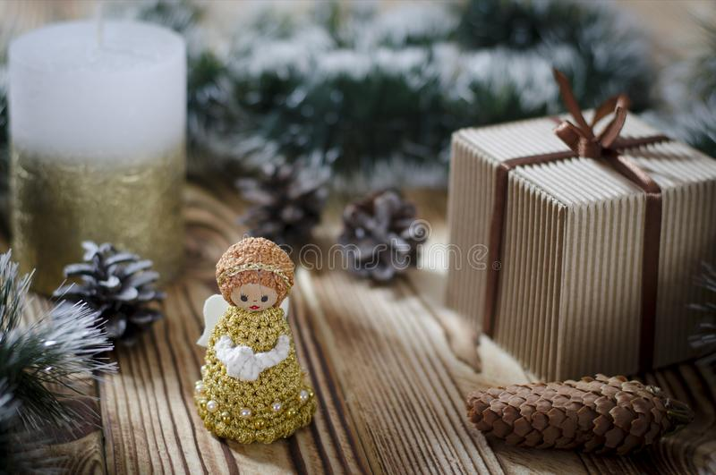 A gift lays on a wooden table next to a candle, cones and an angel against the background of Christmas decorations stock photography