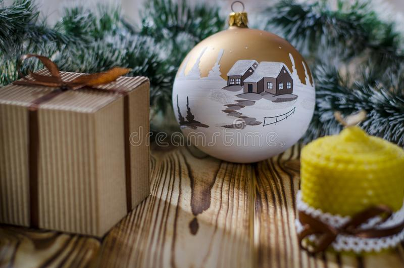 A gift lays on a wooden table next to a candle, cones and an angel against the background of Christmas decorations stock image