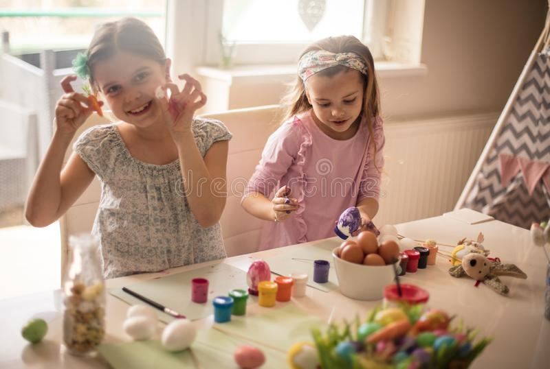 This is a gift for the little Easter bunny. Little girls coloring Easter egg royalty free stock photography