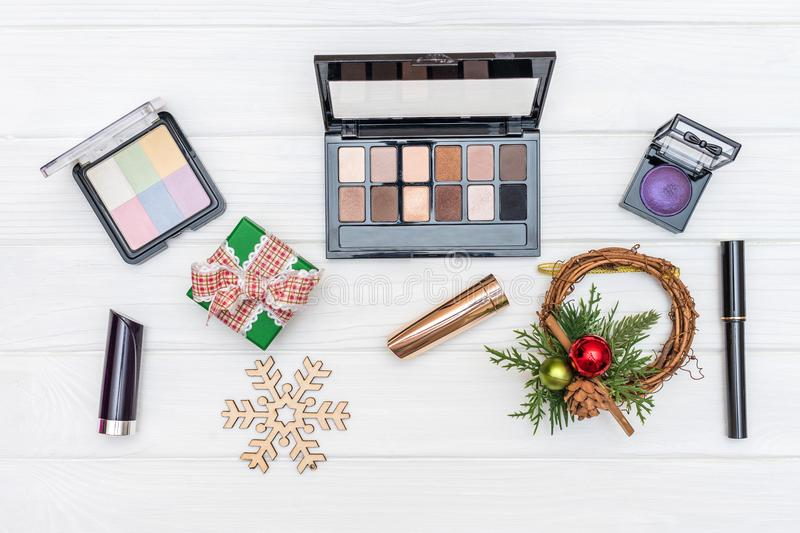 Gift make up, cosmetics and New Year ornaments and toys on white wooden background stock images