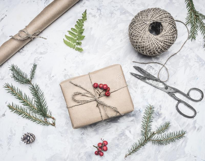 Gift for a new year or Christmas, next to it is a roll of paper, vintage scissors, twigs of Christmas trees and berries of mountai. Gift for a new year Christmas stock photos