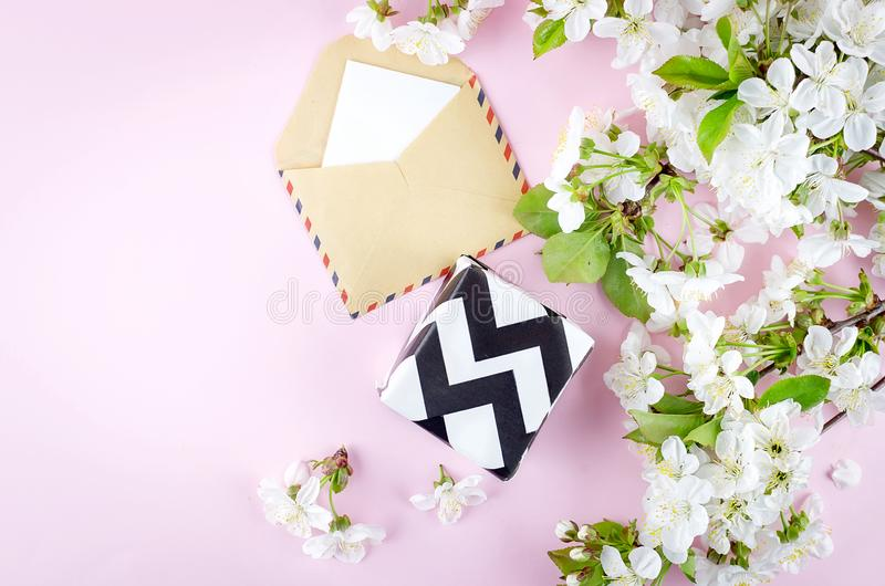 gift and note with cherry flowers on a pink background stock photo