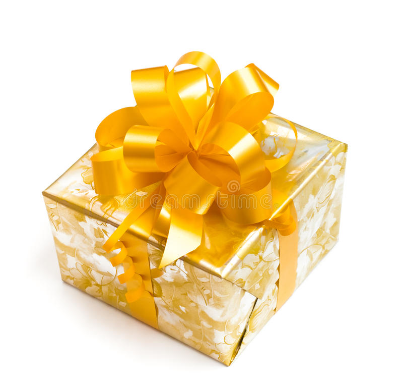 Gift packed in golden paper with yellow bow royalty free stock photography