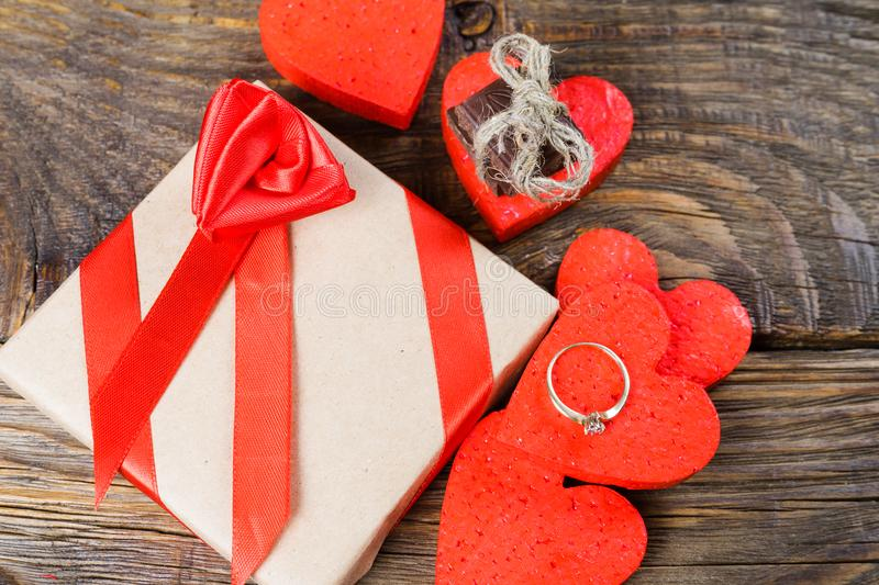 The gift is Packed in Kraft paper and tied with a red ribbon rose. Gift surrounded by decorative hearts one is a wedding ring. With a stone other pieces of stock photos