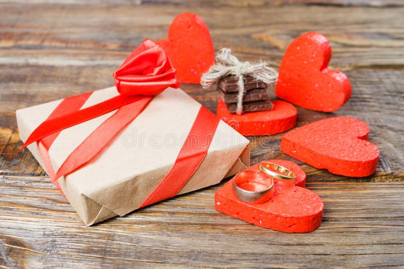 The gift is Packed in Kraft paper and tied with a red ribbon rose. Gift surrounded by decorative heart on one are wedding rings on stock photo