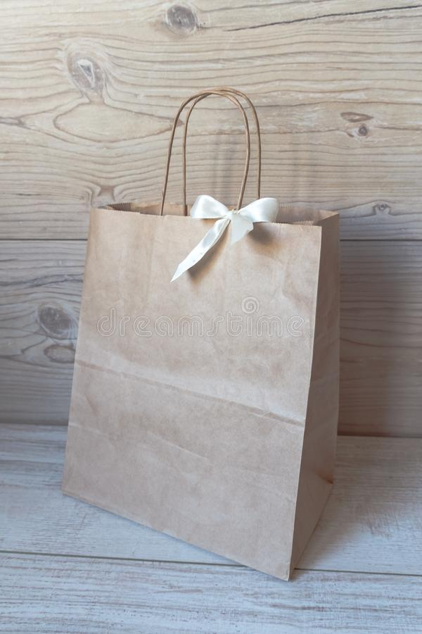 Gift paper bag with white bow isolated in grey wood backgraund. Craft paper shopping bag. Gift paper bag with white bow isolated in grey wood backgraund stock photography