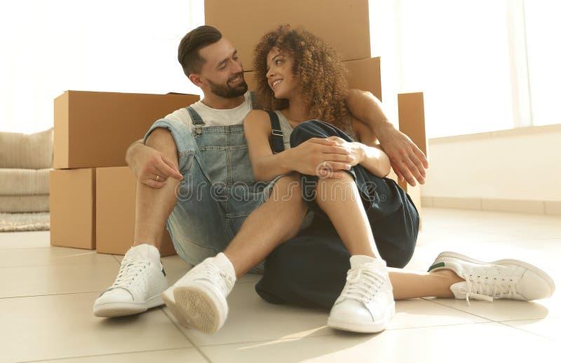 Gift par som sitter nära kartonger i en ny lägenhet royaltyfria foton