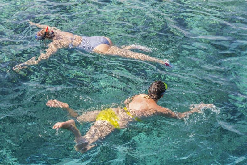 Gift par som snorklar i tropiskt vatten p? semester Kvinnasimning i det bl?a havet Snorkla flickan i rakt framifr?n snorkla maske arkivfoton